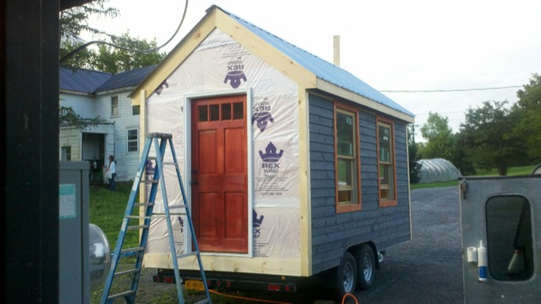 House wrap, siding, and windows installed on tiny house