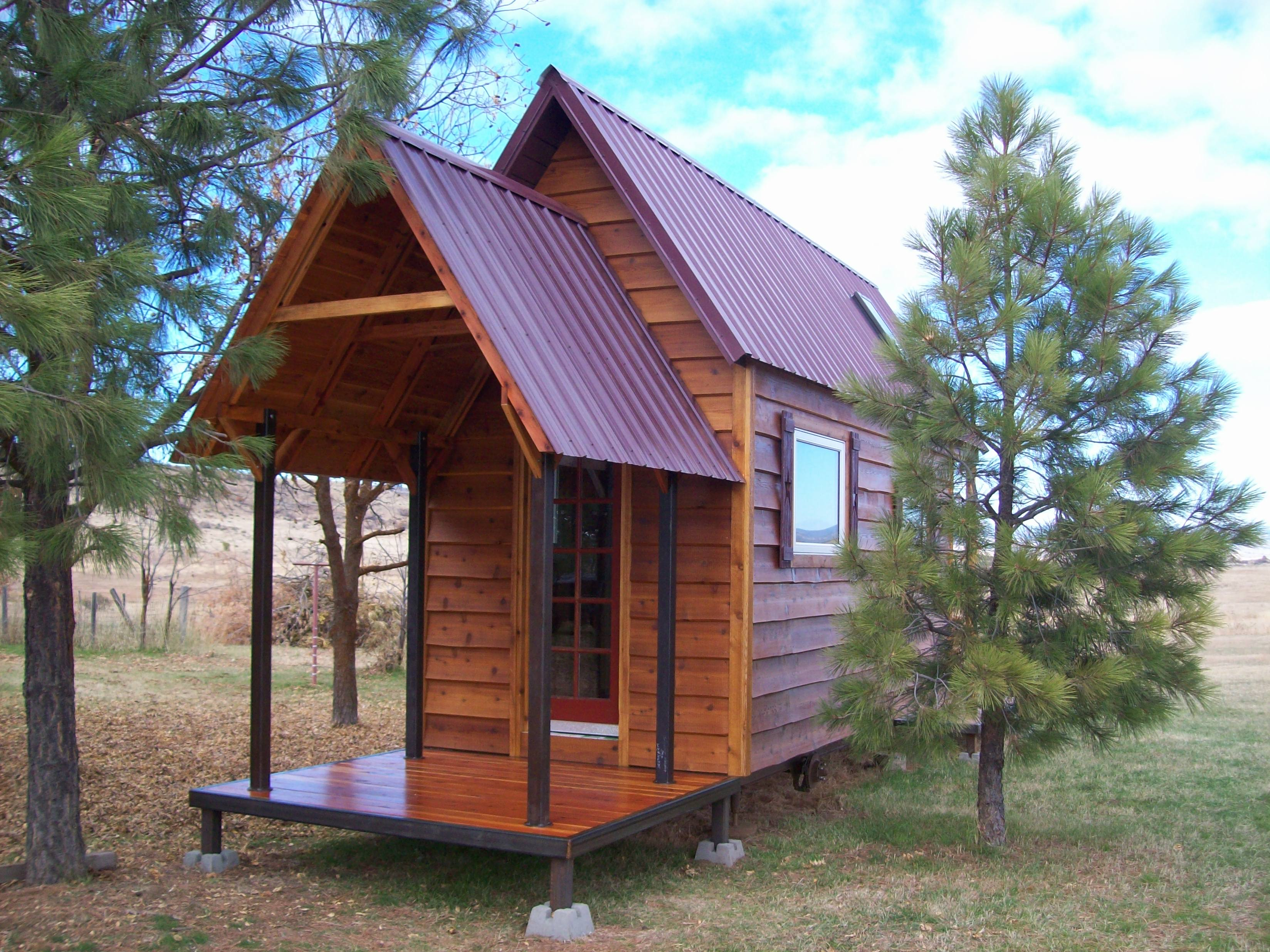 tall tiny house with a porch and loft