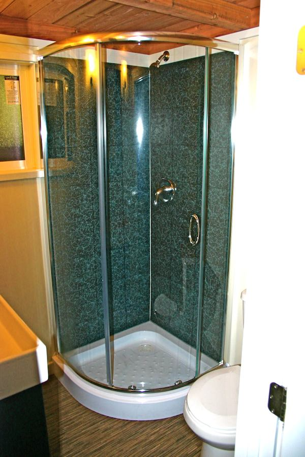 Bathroom with glass stand up shower in a tiny house on wheels