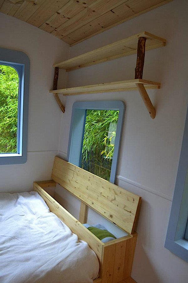 Bed With Storage and Natural Shelving Inside Tiny Caravan on Wheels