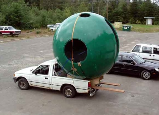 Green sphere tree house being transported by little pickup truck